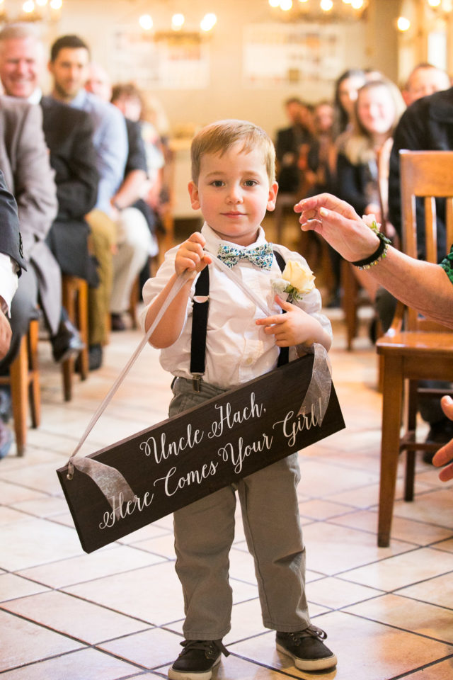 Little boy holds wedding sign at the wedding of Jessica and Justin