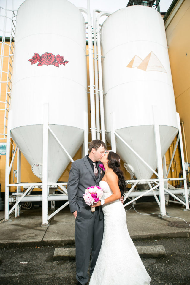 Jessica and Justin kiss by the beer distillery at Portland Brewing Company