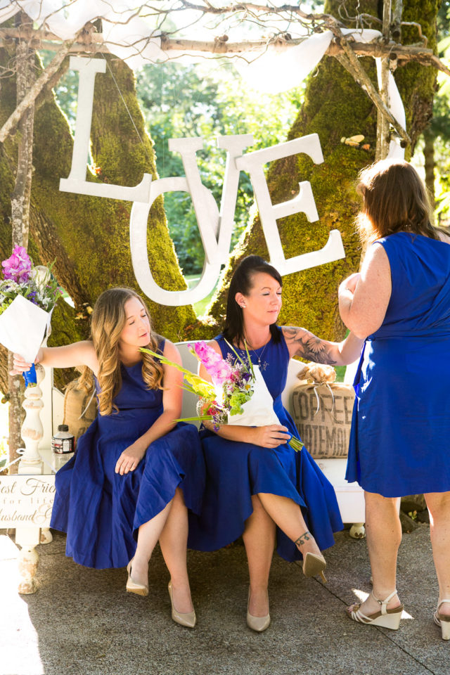 "Bridesmaids at the wedding of Van & Chavala in front of the word ""love"""